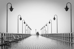 two adult singles walk to restaurants near marina bay in the rain.