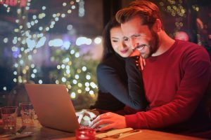couple on computer search for dating websites boston.