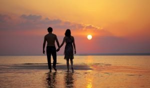 Dating in your 20s includes handheld walks on the beach at Sunset.