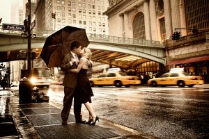A couple embraces in the rain in downtown Boston, proving dates in Boston should always include an umbrella.