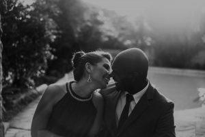 A heterosexual couple embraces on a black tie, professional date.