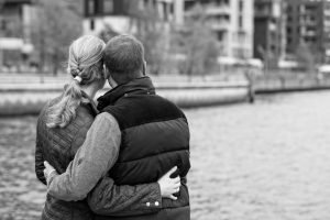 A couple embraces while looking over the river, one of the top dating sites in Boston.